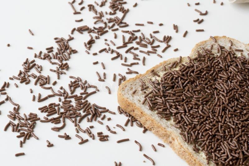 Skiva av chokladhagel f?r brunt br?d, holl?ndsk hagelslag, mot vit tgle arkivbild