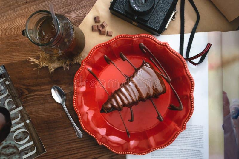 Skiva av chokladkakan på en röd platta arkivfoton