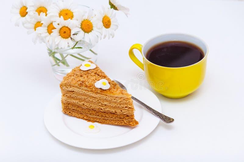 Skiva av den hemlagade lagerhonungkakan med den gula kopp te eller kaffe och kamomillar royaltyfri foto