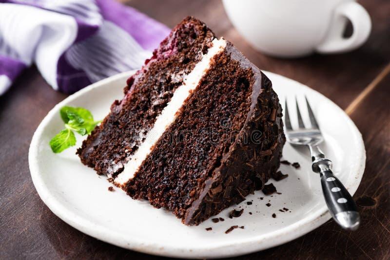 Skiva av den mörka chokladkakan på plattan royaltyfri bild