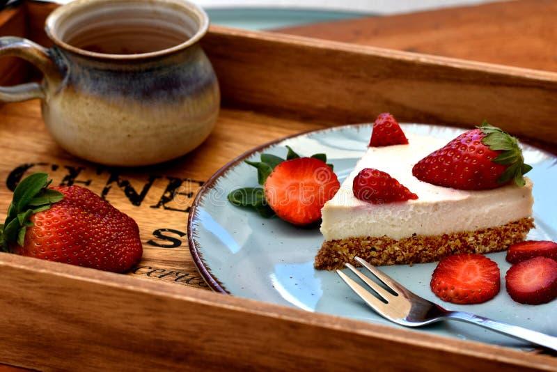 Skiva av den rå vita jordgubbekakan på en blå platta med koppen kaffe sunt frukostbegrepp royaltyfria foton