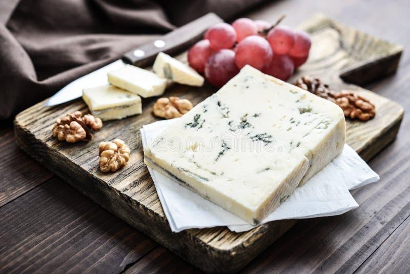 Skiva av Gorgonzola ost på skärbräda royaltyfri foto