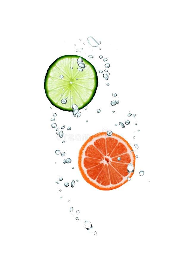Skiva av grapefrukten och limefrukt i vatten royaltyfria foton
