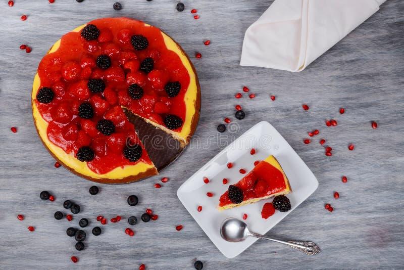 Skiva av jordgubbeostkaka på den vita plattan royaltyfria foton
