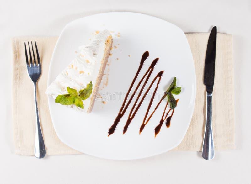 Skiva av kakan med piskad kräm på plattan royaltyfria foton