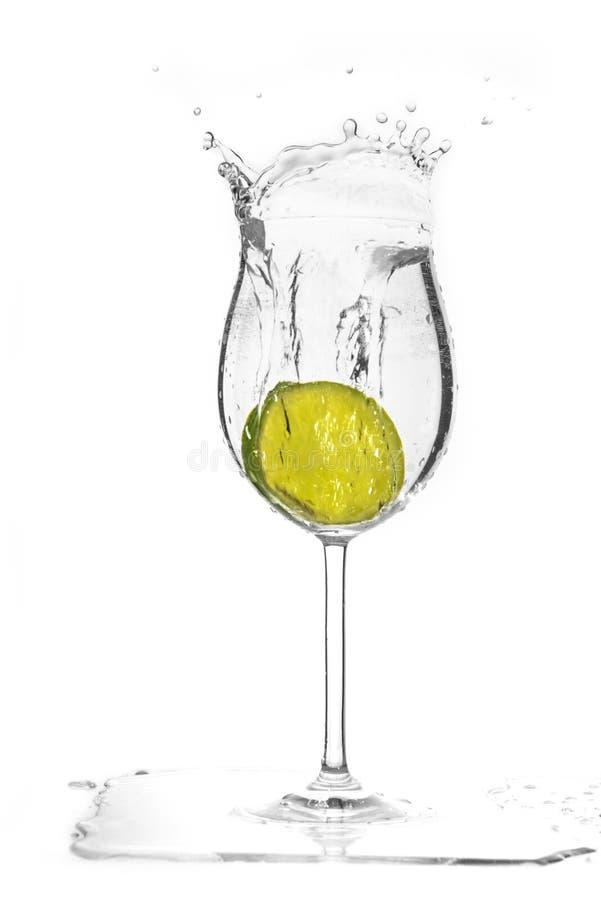 Skiva av limefruktdroppen i glass orsak färgstänket royaltyfria bilder