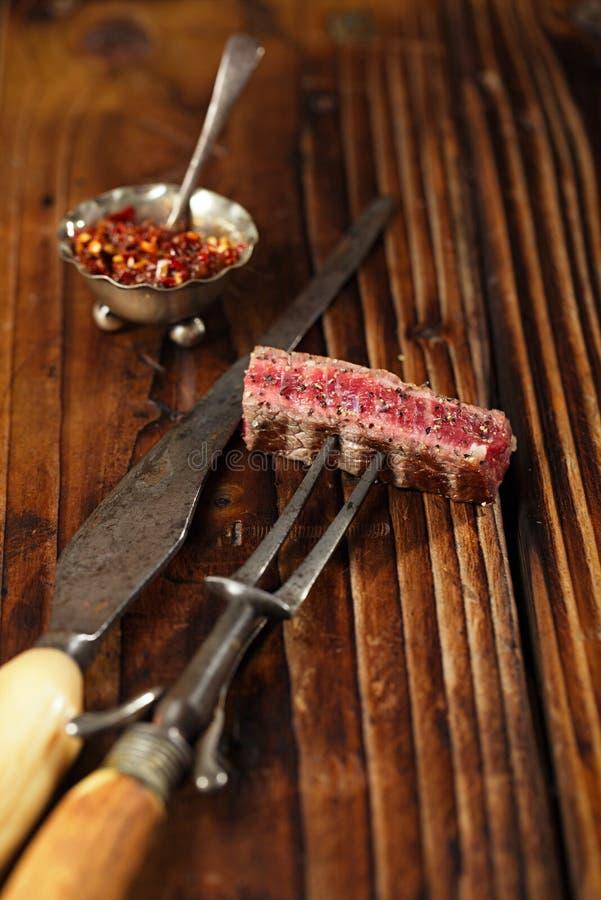 Skiva för nötköttbiff på tappningköttgaffel royaltyfri bild