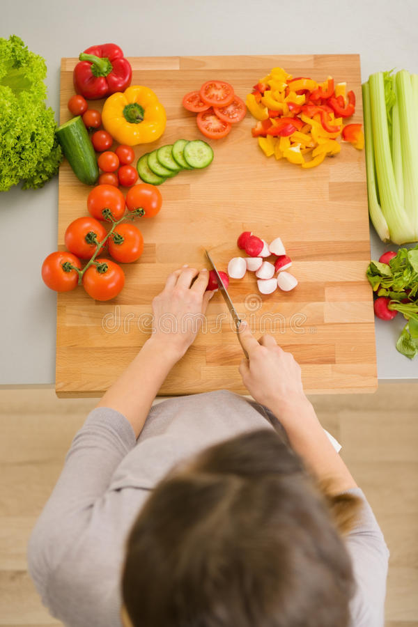Skiva grönsaker för kvinna på skärbräda royaltyfri foto
