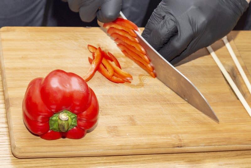 Skiva paprikakocken laga mat sund mat banta sund mat träskärbräda på trätabellen, kockhänder i svart gummiglo arkivfoton