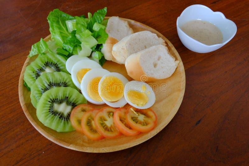Skivad äggsalladserve med grönsaken, kiwin, tomaten, frasigt bröd och den avskilda sesamdressingen royaltyfri foto