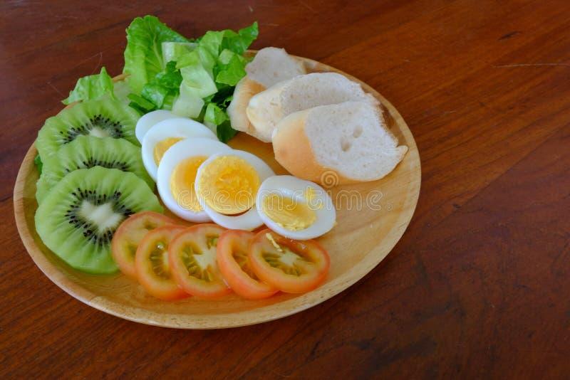 Skivad äggsalladserve med grönsaken, kiwin, tomaten och frasigt bröd arkivfoto
