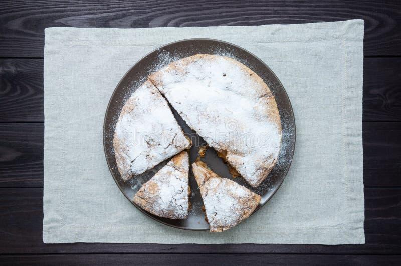 Skivad äppelpaj i platta på mörk träbakgrund royaltyfri foto