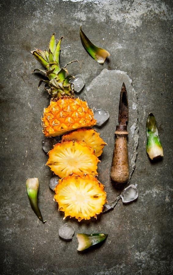 Skivad ananas med en kniv och sidor på en sten står royaltyfri fotografi