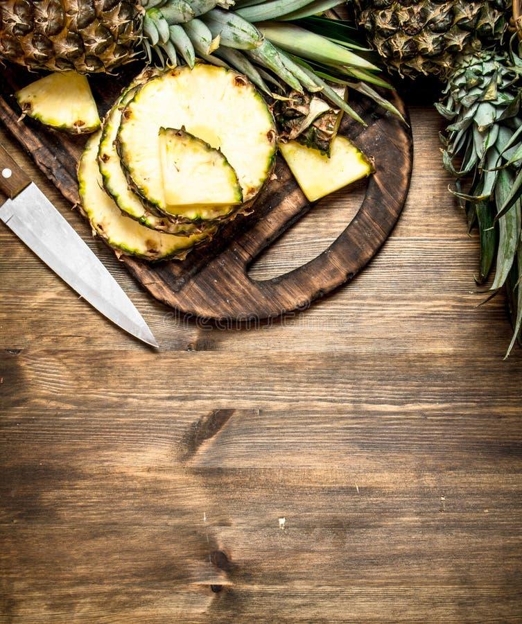Skivad ananas på en skärbräda med en kniv arkivfoto