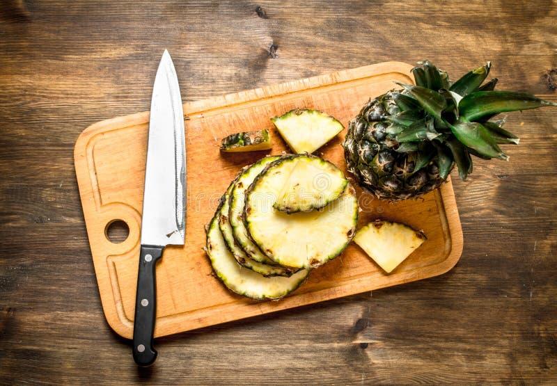 Skivad ananas på en skärbräda med en kniv royaltyfri fotografi