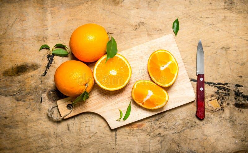 Skivad apelsin på ett träbräde med sidor royaltyfri bild