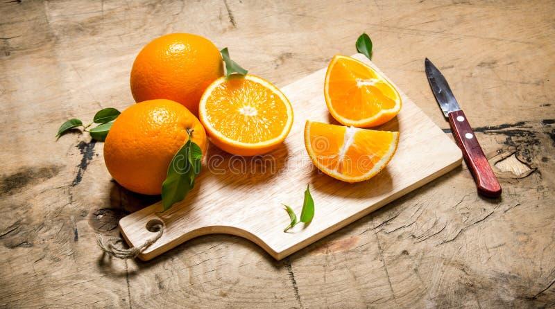 Skivad apelsin på ett träbräde med sidor arkivbild