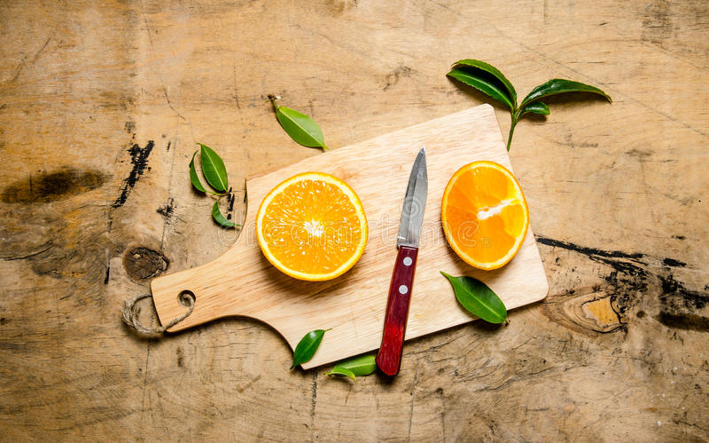 Skivad apelsin på ett träbräde med sidor arkivfoton