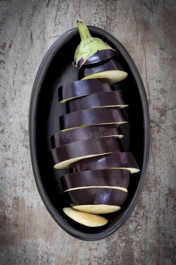 Skivad aubergine i svart maträtt royaltyfri fotografi