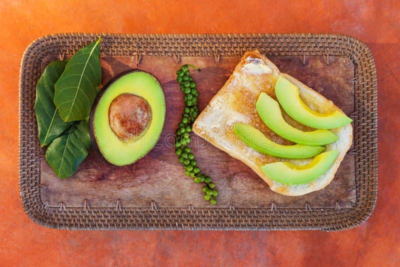 Skivad avokado på bröd med det nya gröna pepparkornet royaltyfri bild