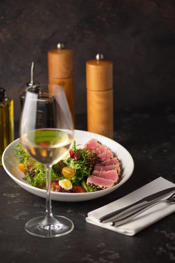 Skivad biff av tonfisk i sesam och en sallad arkivfoto