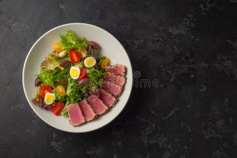 Skivad biff av tonfisk i sesam och en sallad av nya grönsaker och vaktelägg royaltyfri bild