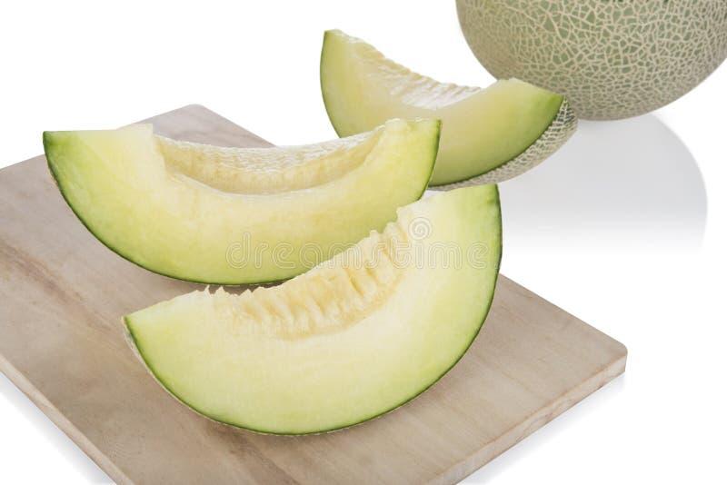 Skivad cantaloupmelonmelon och halv cantaloupmelonmelon på på träskärbräda och träbakgrund arkivfoton
