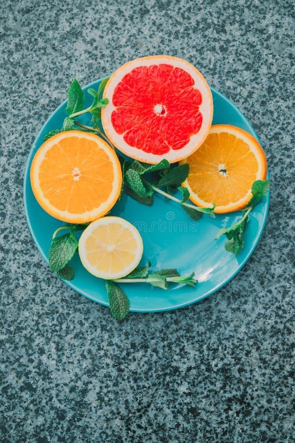 Skivad citron, apelsin, grapefrukt och mintkaramell på en blå platta, vitaminer, citrus i minimalismstil, popkonst royaltyfri foto