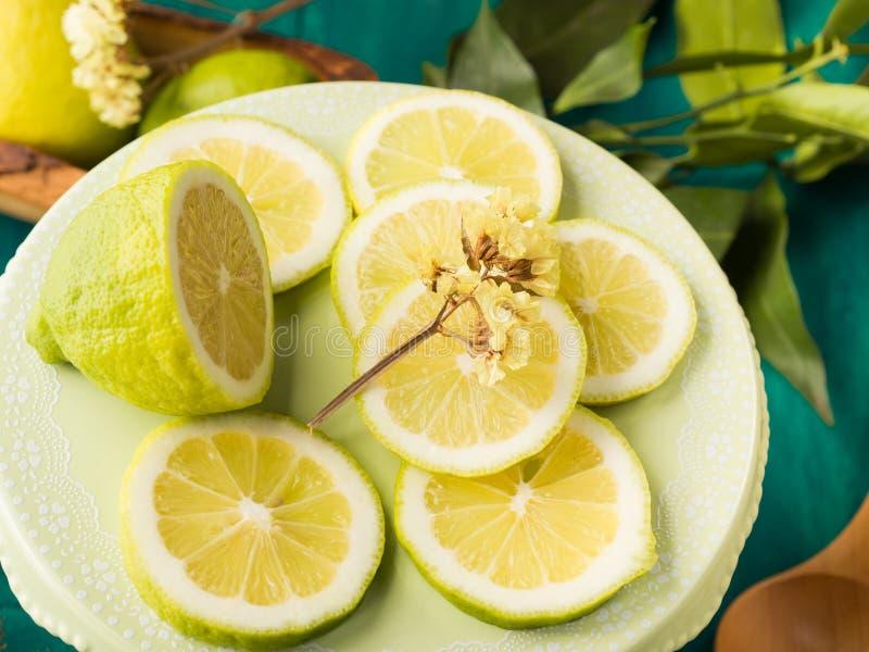Skivad citron på grön bakgrund arkivbilder