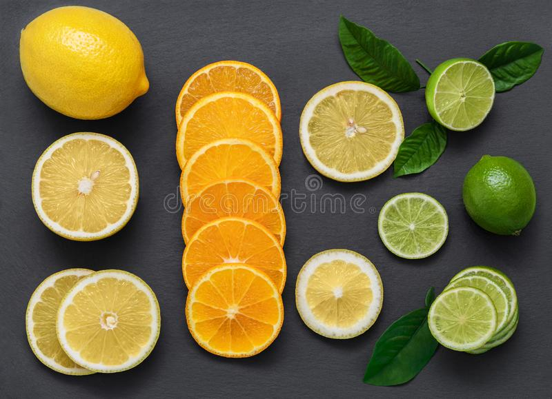 Skivad citrusfrukt på en stentabell Saftiga mogna skivor av apelsinen, citronen och limefrukt på en svart bakgrund Fruktblandning arkivbild