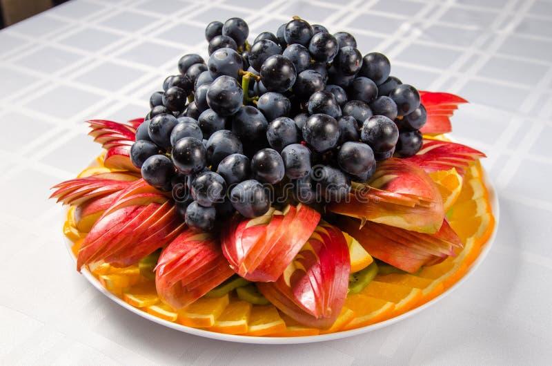 Skivad frukt - äpplen, apelsiner, kiwi som överträffas med druvor på den vita maträtten arkivbilder