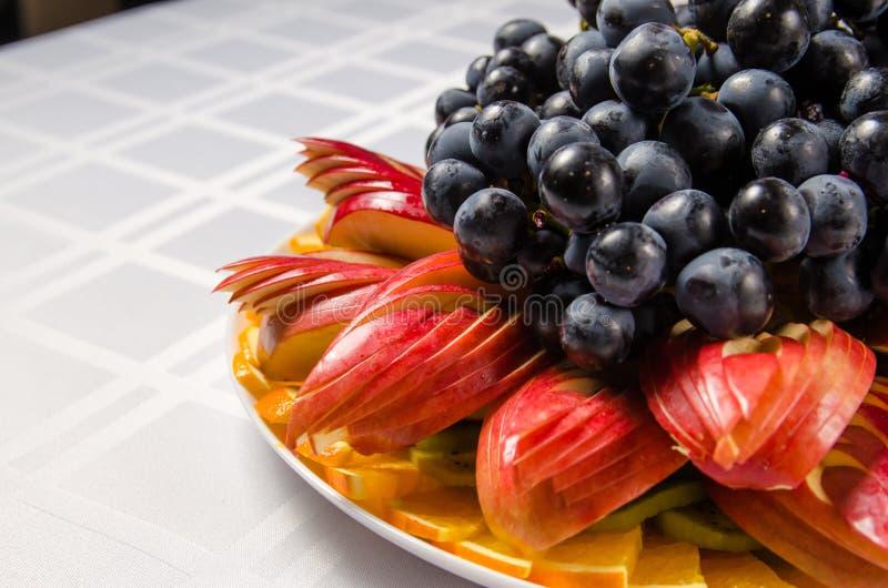Skivad frukt - äpplen, apelsiner, kiwi som överträffas med druvor på den vita maträtten arkivbild