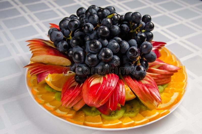 Skivad frukt - äpplen, apelsiner, kiwi som överträffas med druvor på den vita maträtten royaltyfria foton