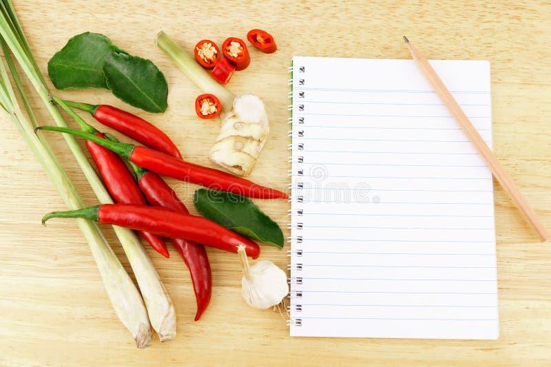 Skivad glödhet chilipeppar med bergamotsidor, vitlök, galangal och citrongräs och anteckningsbok med blyertspennan arkivbild