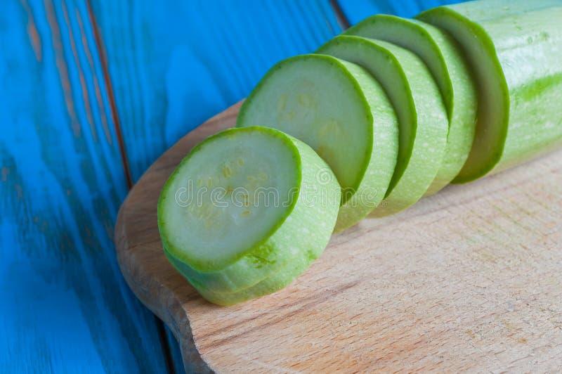 Skivad grönsakmärg på ett lantligt blått trä arkivfoto