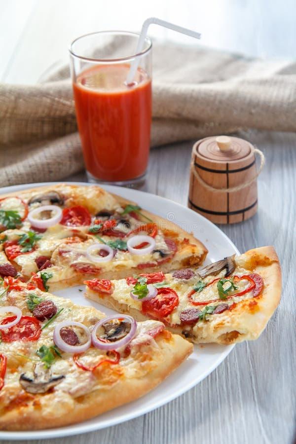 Skivad hel ny pizza med tomater, salami, ost och mushr royaltyfri fotografi