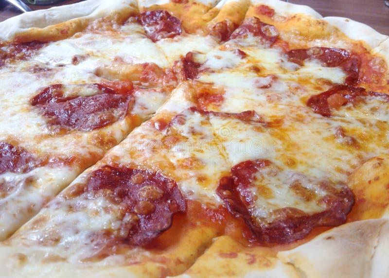 Skivad hel salamipizza på en trätabell fotografering för bildbyråer
