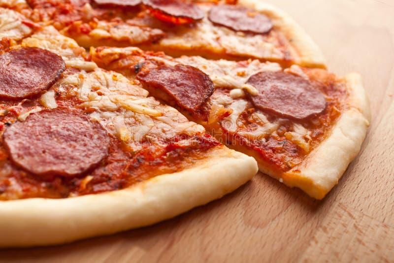 Skivad hel salamipizza på trätabellen fotografering för bildbyråer