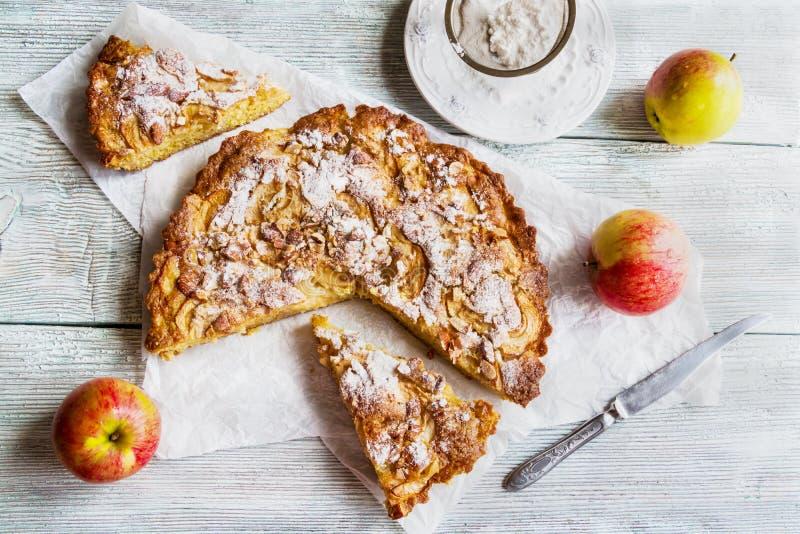 Skivad hemlagad äpple- och mandelkaka på träbakgrund royaltyfri foto