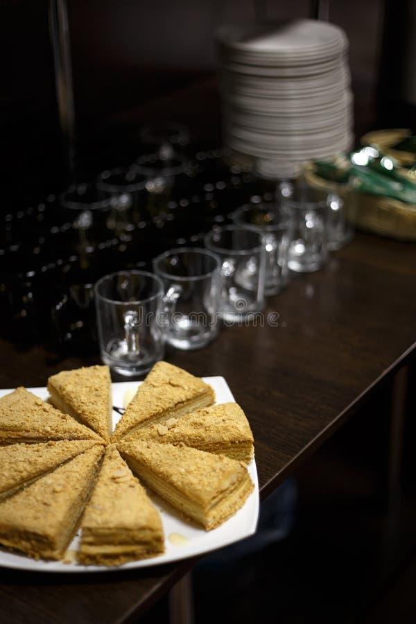 Skivad kaka på den vita plattan bredvid den emty koppar och högen av plattor på trästångräknare fotografering för bildbyråer