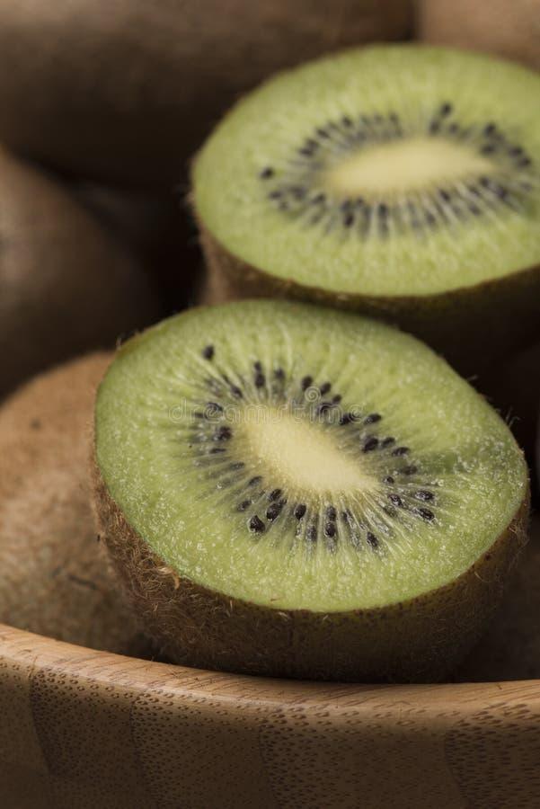 Skivad kiwi för ‹för †i bunke på träbakgrund stock illustrationer