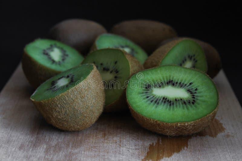 Skivad kiwi i träbrädet, slut upp grön frukt, mörk bakgrund royaltyfri bild