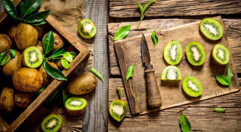 Skivad kiwi på det gamla brädet med kniven och asken fotografering för bildbyråer