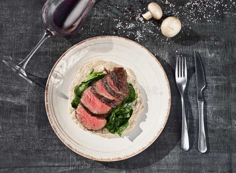 Skivad medelsällsynt grillad nötköttbiff med champinjonsås och gräsplaner på en platta på träbakgrund royaltyfri foto