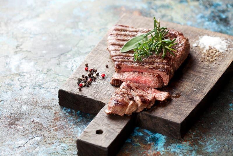 Skivad medelsällsynt grillad nötköttbiff på träskärbräda royaltyfria foton