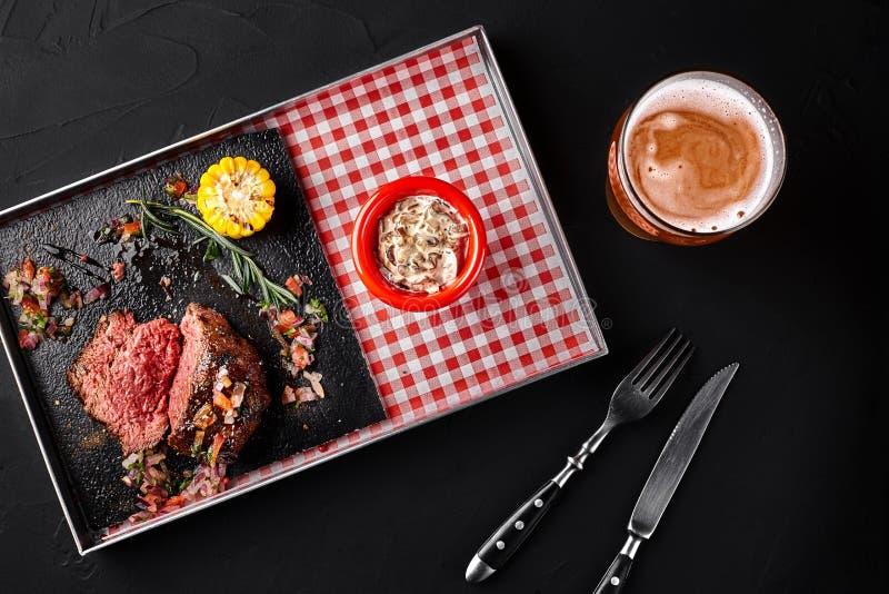 Skivad medelsällsynt grillad nötköttbiff Ribeye med havre-, rosmarin-, lök- och champinjonsås på ett metallmagasin på en svart arkivfoton