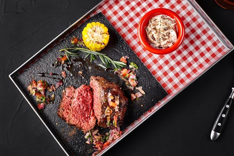 Skivad medelsällsynt grillad nötköttbiff Ribeye med havre-, rosmarin-, lök- och champinjonsås på ett metallmagasin på en svart arkivbilder