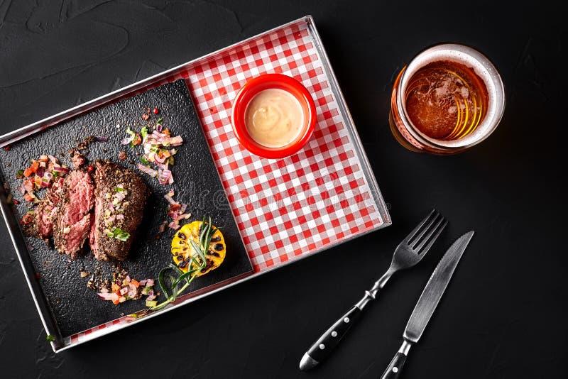 Skivad medelsällsynt grillad nötköttbiff Ribeye med havre, rosmarin, löken och vit sås på ett metallmagasin på en svart arkivbild