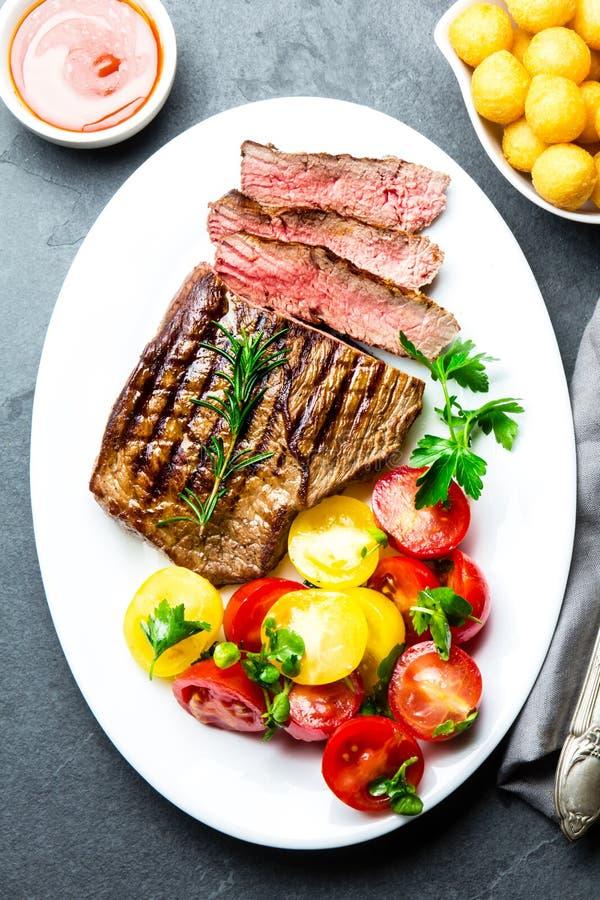 Skivad medelsällsynt grillad nötköttbiff tjänade som på den vita plattan med tomatsallad och potatisbollar Grillfest bbq-kött fotografering för bildbyråer