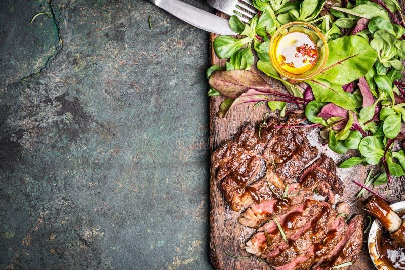 Skivad medelsällsynt grillad nötköttgrillfestbiff med nytt grön sallad och bestick på lantlig bakgrund, bästa sikt arkivfoto